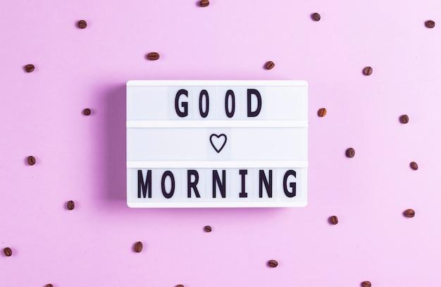 Inscrição bom dia em um quadro branco em um fundo rosa com grãos de café