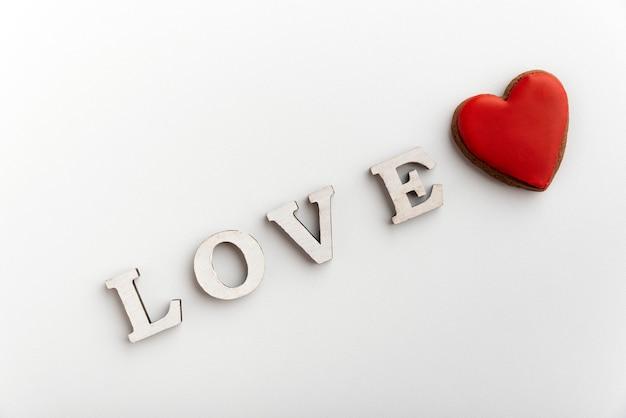 Inscrição branca de amor na superfície branca ao lado do coração vermelho