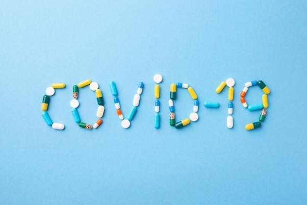Inscrição covid-19 em formação médica azul feita de comprimidos e cápsulas