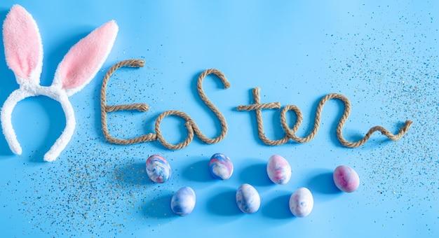 Inscrição criativa de páscoa em azul com itens de decoração de páscoa.