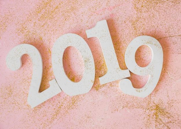 Inscrição de 2019 branco na mesa-de-rosa
