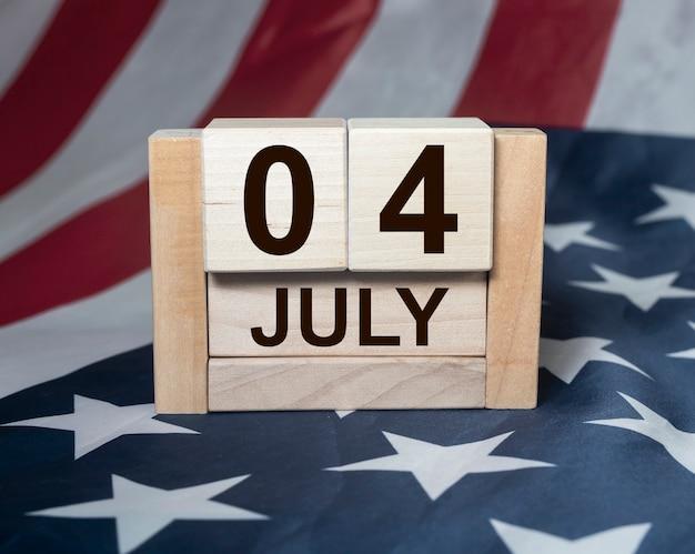 Inscrição de 4 de julho no calendário de madeira da bandeira americana Foto Premium