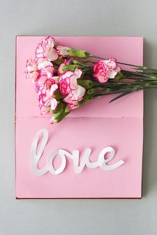 Inscrição de amor branco com flores no caderno