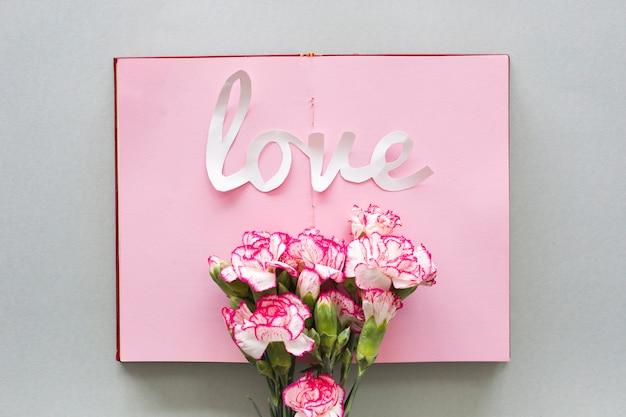 Inscrição de amor com flores no caderno