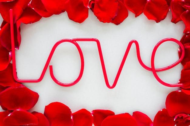 Inscrição de amor com pétalas de rosa na mesa cinza