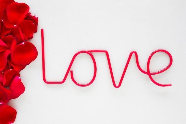 Inscrição de amor com pétalas de rosa na mesa de luz