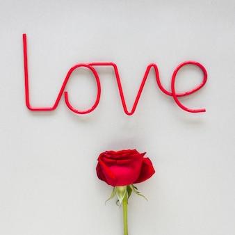 Inscrição de amor com rosa vermelha na mesa