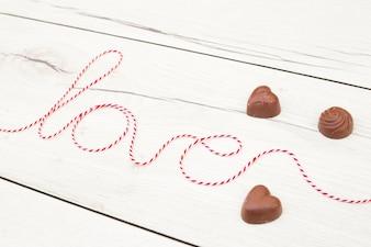 Inscrição de amor de fio perto de corações de chocolate