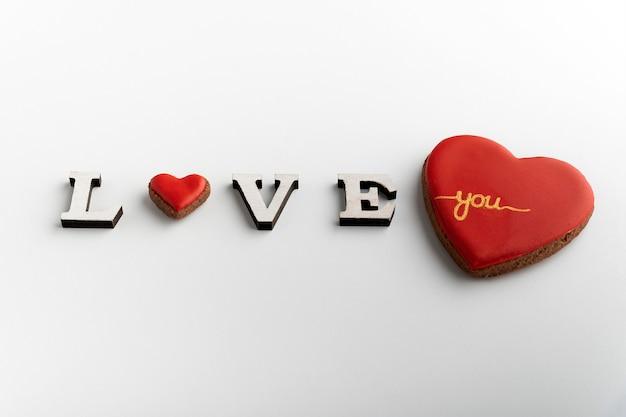 Inscrição de amor em fundo branco com coração em vez da letra o e um grande coração vermelho.