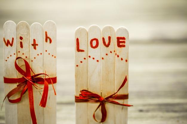 Inscrição de amor para o dia dos namorados em pequenas varas de madeira com um coração