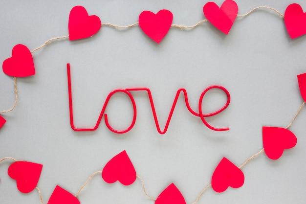 Inscrição de amor vermelho com corações de papel