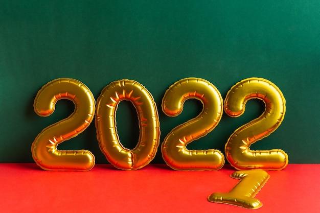 Inscrição de ano de números dourados em fundo verde e vermelho