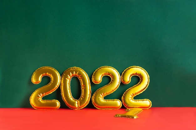 Inscrição de ano de números dourados em superfície verde irregular e fundo vermelho