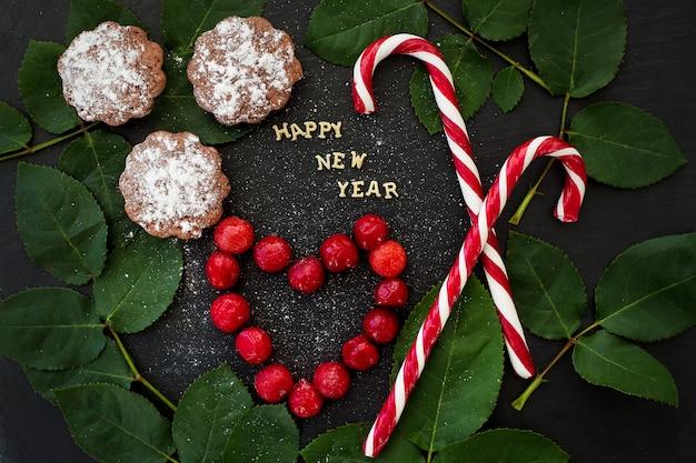 Inscrição de ano novo em uma placa preta com cupcakes e doces vermelhos