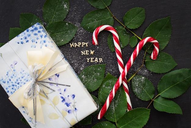 Inscrição de ano novo em uma placa preta com doces presente e vermelho