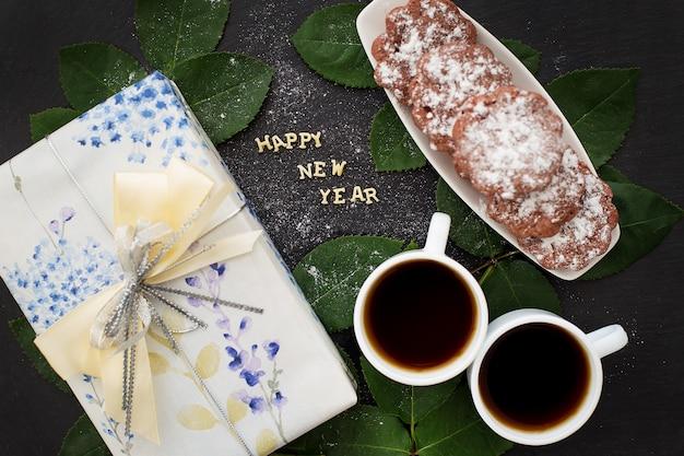 Inscrição de ano novo em uma placa preta com presente, bolos e café