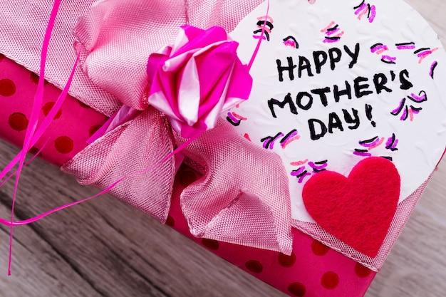 Inscrição de cartão de feliz dia das mães. laço rosa na caixa de presente. saudação composição artesanal. envie os melhores votos.