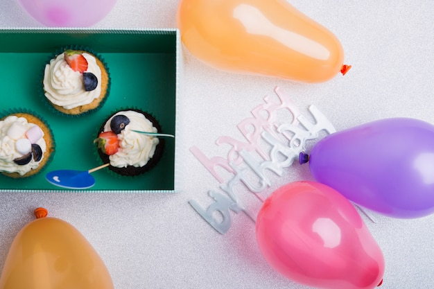 Inscrição de feliz aniversário com cupcakes na mesa