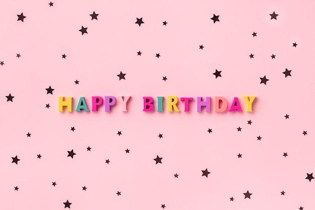 Inscrição de feliz aniversário com letras coloridas de madeira com confete