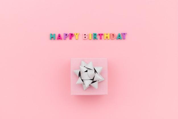 Inscrição de feliz aniversário com letras coloridas de madeira e caixa de presente