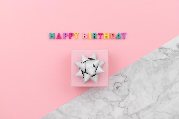 Inscrição de feliz aniversário de letras coloridas de madeira com caixa de presente.