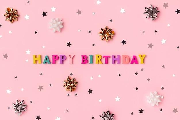 Inscrição de feliz aniversário de letras coloridas de madeira com confete estrela.