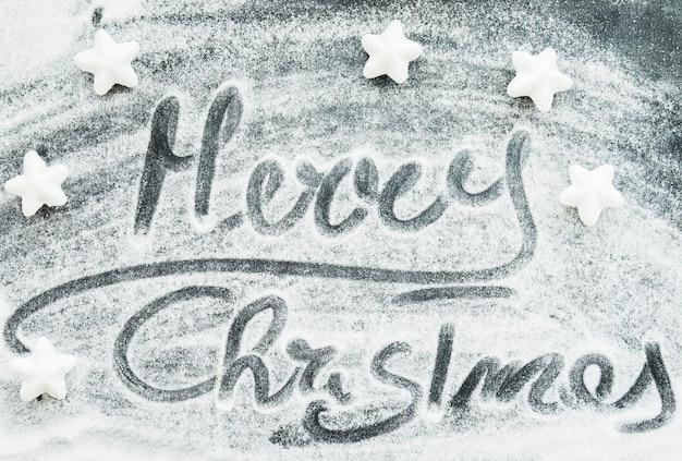 Inscrição de feliz natal entre neve decorativa e estrelas