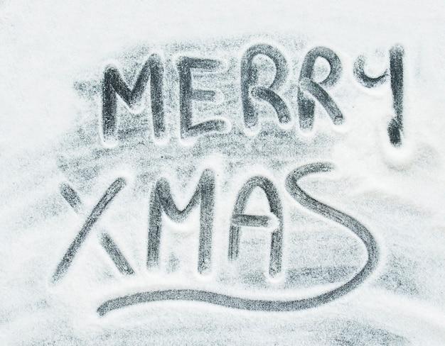 Inscrição de feliz natal entre neve decorativa