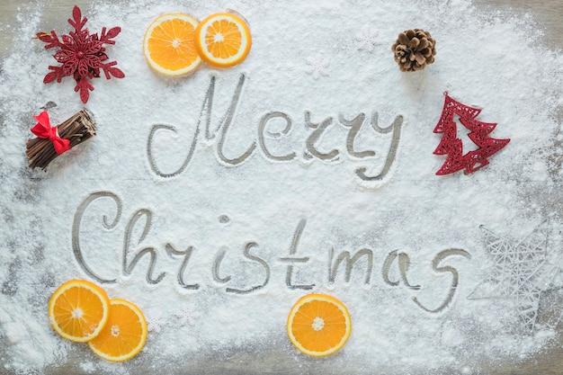Inscrição de feliz natal na neve perto de laranjas e decorações