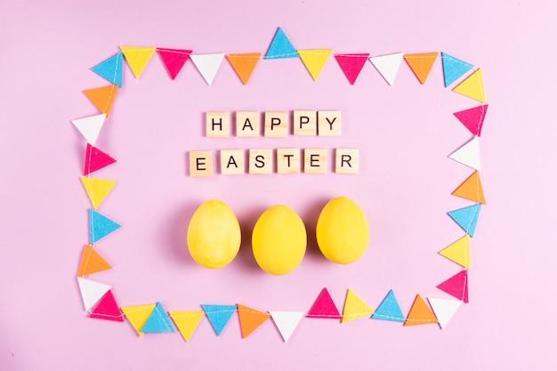 Inscrição de feliz páscoa em letras de madeira com ovos pintados de amarelo em uma moldura feita de guirlanda multicolorida de feltro em um fundo rosa