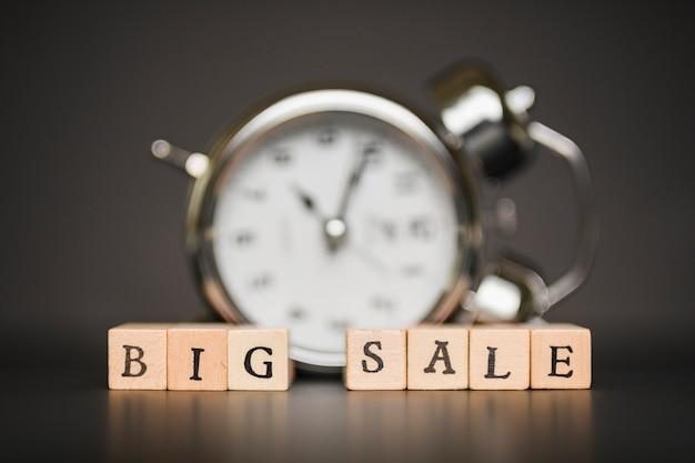 Inscrição de grande venda em blocos de madeira com relógio