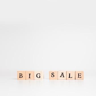 Inscrição de grande venda em blocos de madeira na mesa