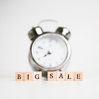 Inscrição de grande venda em pequenos blocos de madeira com relógio