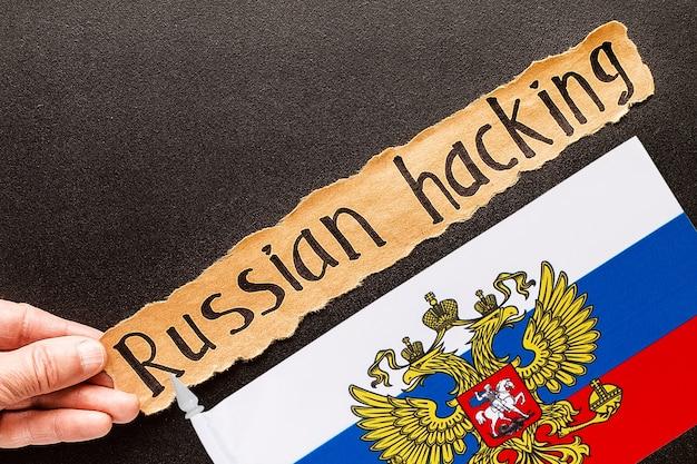 Inscrição de hackers russos na folha de papel rasgado