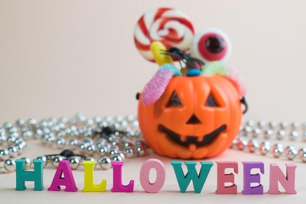 Inscrição de halloween no fundo de uma abóbora com doces.