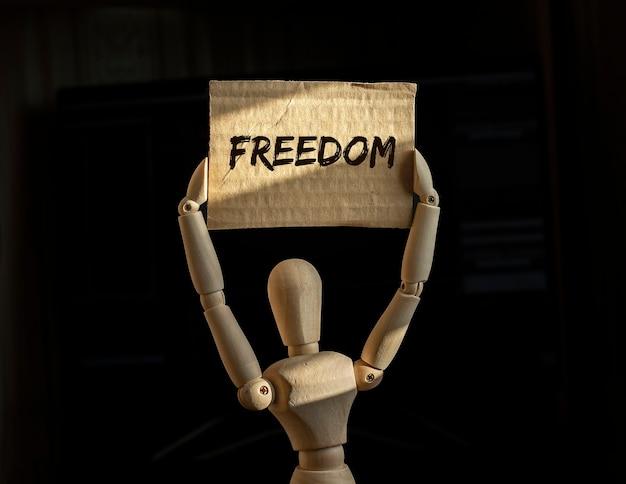 Inscrição de liberdade no cartaz do manifestante de madeira abstrato.