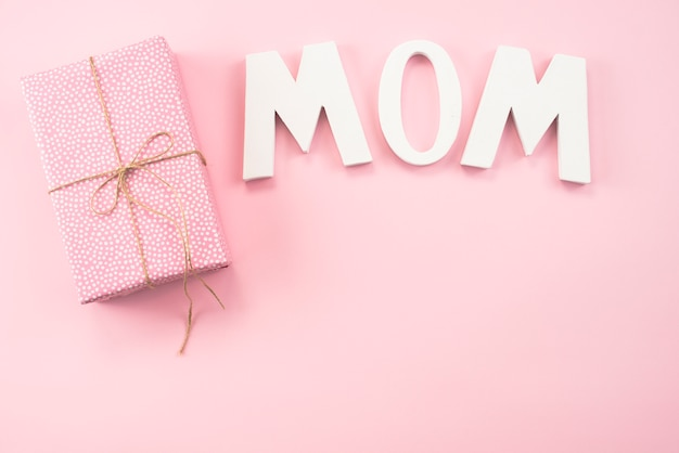 Inscrição de mãe com caixa de presente na mesa