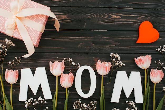 Inscrição de mãe com tulipas e presente na mesa