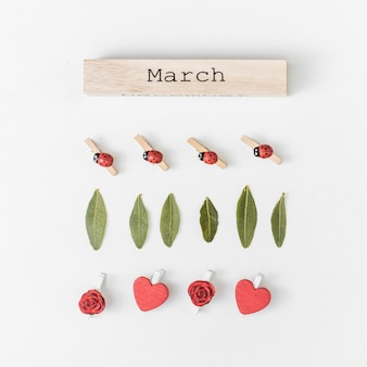 Inscrição de março com folhas verdes e flores