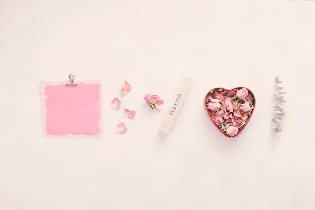 Inscrição de março com papel pequeno e pétalas de rosa