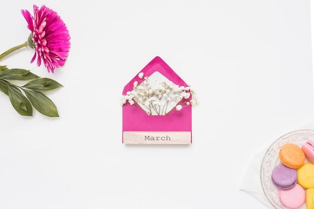 Inscrição de março com ramos de envelope e flor