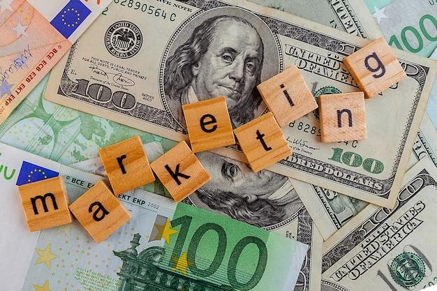 Inscrição de marketing em cubos de madeira na textura de notas de dólares e euros