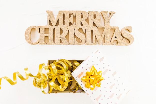 Inscrição de natal feliz decorativa perto de caixa de presente com fita