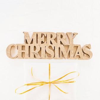 Inscrição de natal feliz decorativa perto de caixa de presente no envoltório