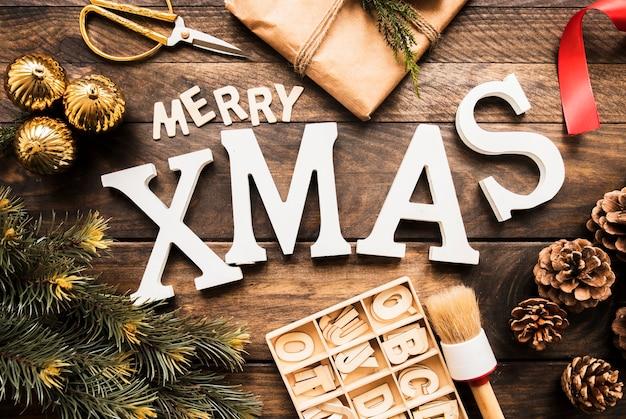 Inscrição de natal feliz perto de galho de coníferas, caixa de presente e letras