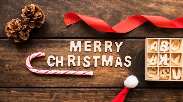 Inscrição de natal feliz perto de senões, bastão de doces e fita