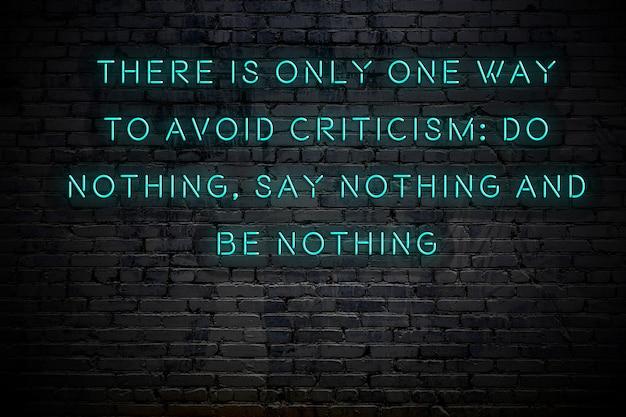 Inscrição de néon de citação motivacional sábia positiva contra a parede de tijolos