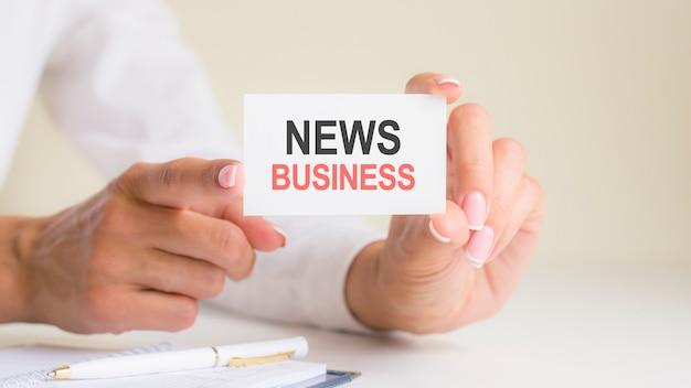 Inscrição de notícias de negócios na folha de papel cartão branco nas mãos da mulher. letras pretas e vermelhas em papel branco. conceito de negócio, fundo cinza