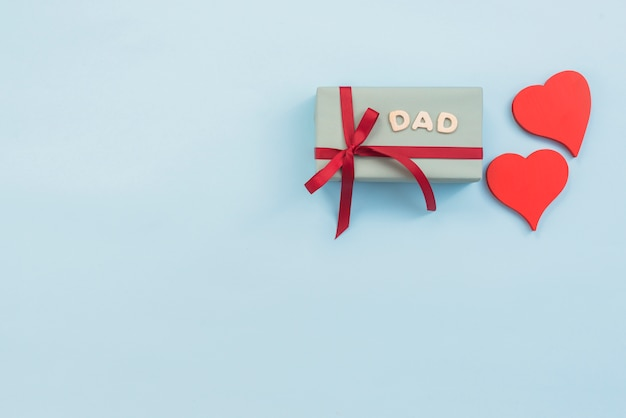 Inscrição de pai com caixa de presente e corações vermelhos