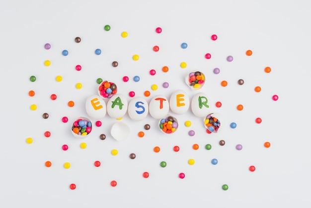 Inscrição de páscoa em ovos com doces na mesa de luz